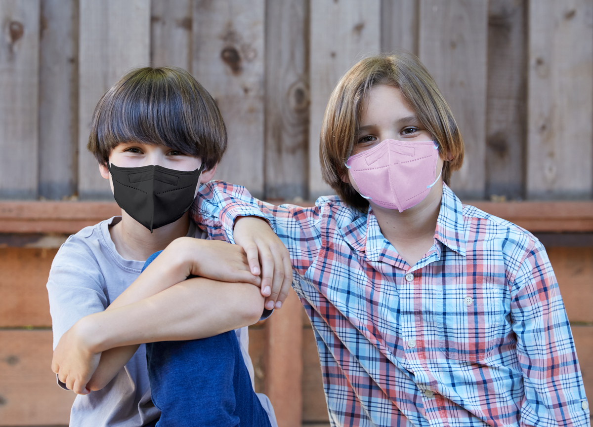 Two boys sitting together with masks on